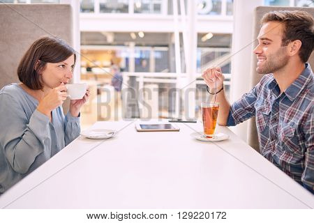 Handsome man and attractive foreign woman smiling and looking into each others eyes. Their first date is going rather well and they both have interest in one and other.