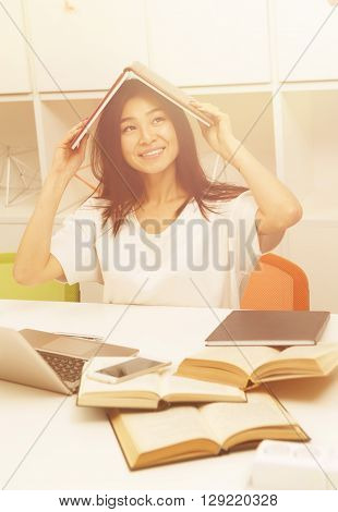 Toned image. Portrait of happy Asian student lady witting in library with exercise-book above her head. Beautiful woman studying on laptop computer.