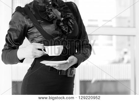 slim well-dressed woman holding a cup of coffee