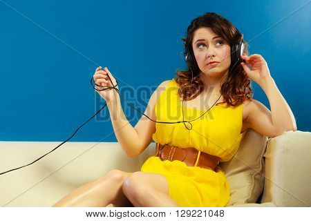 Young people leisure relax concept. Teen cute girl yellow dress in big headphones listening music mp3 sitting on couch relaxing on blue