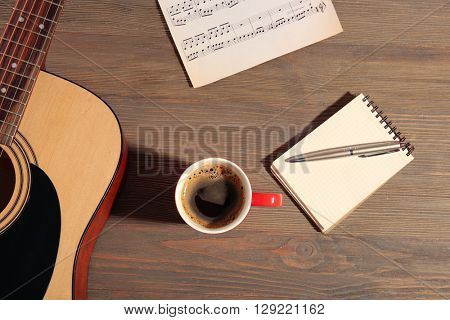 Guitar with notebook and cup of coffee on wooden background