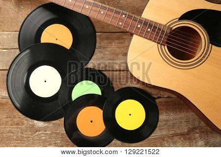 Guitar and gramophone records on wooden background