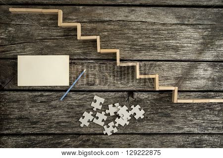 Way to success - top view of wooden pegs forming a staircase on wooden desk with puzzle pieces blank paper and a pencil lying next to it.