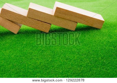 Light brown color Wooden domino on green grass