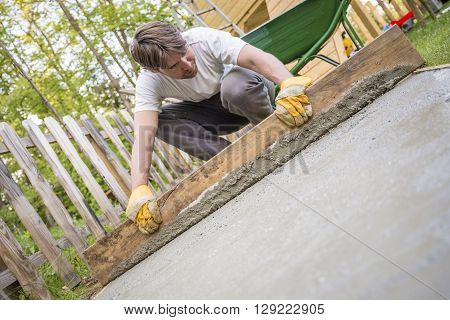 Man leveling the cement in a backyard at home using a wooden plank as he lays a new concrete surface low angle tilted view.