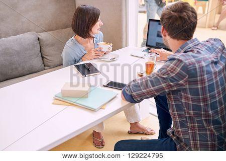 man busy showing his female business partner his budget proposal on his notebook while sitting in a public cafe drinking coffee and tea