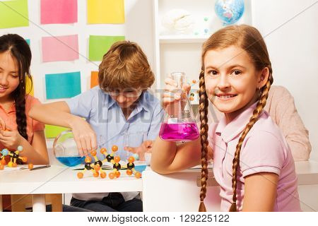 Cute schoolgirl with long plaits holding flask with pink reagent at the school laboratory