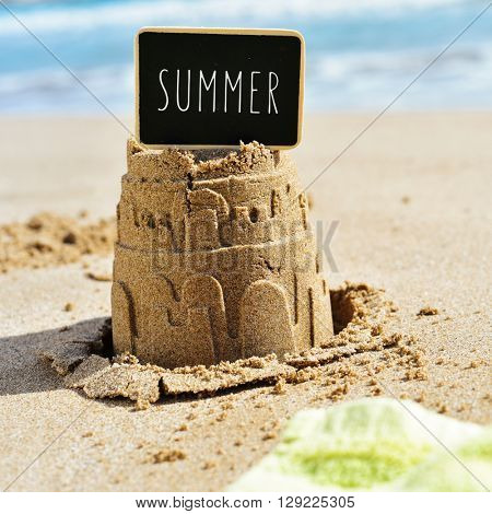 closeup of a sandcastle on the sand of a beach topped with a black signboard with the word summer written in it