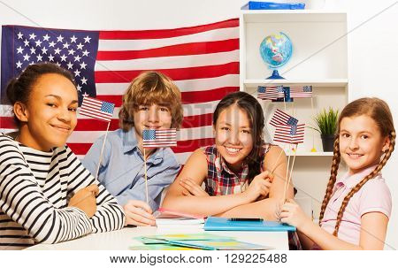 Four happy multiethnic students waving American flags at the geography lesson