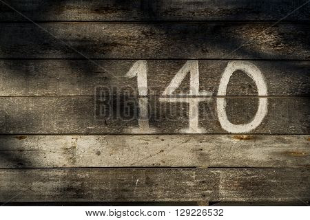A shot of a wooden wall with number 140.