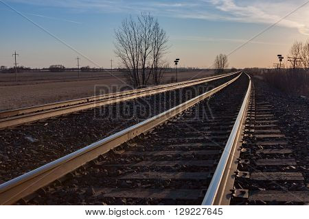 Sun lit tracks heading toward horizon at sunset