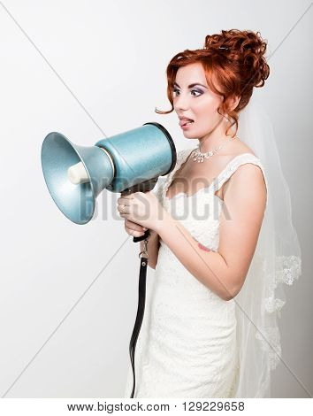 beautiful bride in a wedding dress with a wedding makeup and hairstyle, she yells into a bullhorn. Public Relations.