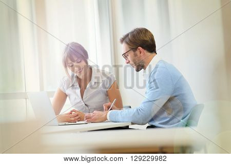 Colleagues working in modern office with laptop