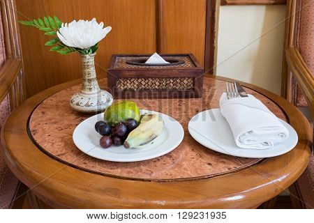 White flower with green leaf in bouquet put in ceramic vase on brown wooden table/ with fruit set of orange, grape and banana White flower in vase on wooden table with fruit set