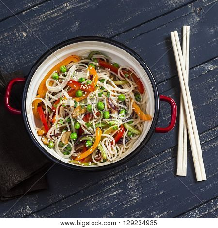Stir fry vegetable with rice noodles in an enamel pot on dark wooden background