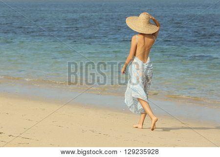 Girl walking on the beach - wearing big straw hat