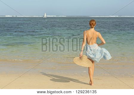 Girl on the beach looking at the horison