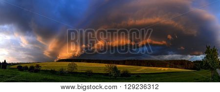 quickly and dramatically evolving the cloudy formation lit by the setting sun over the meadow and a field with blooming rape Zabrehs highlands North Moravia Czech republic panoramic view compiled from six shot