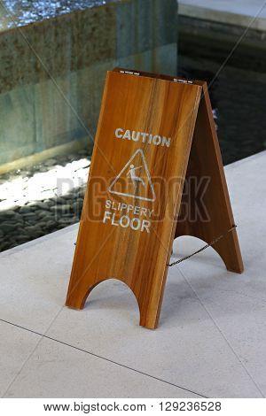 Wooden caution sign of wet floor -