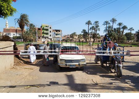 DARAW, EGYPT - FEBRUARY 6, 2016: Vehicles waiting in line at train crossing.