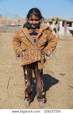 DARAW, EGYPT - FEBRUARY 6, 2016: Portrait of bare feet local girl posing for camera.