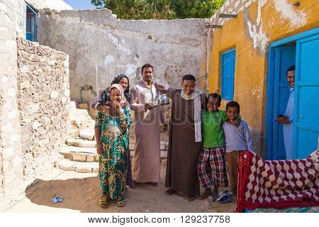 ASWAN, EGYPT - FEBRUARY 7, 2016: Local family posing in front of the house in Nubian village on the Nile.