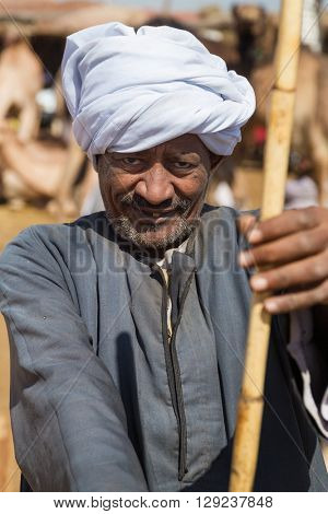 DARAW, EGYPT - FEBRUARY 6, 2016: Portrait of elderly camel salesman with stick at Camel market.