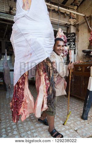 DARAW, EGYPT - FEBRUARY 6, 2016: Local butcher posing by piece of meat in the shop.