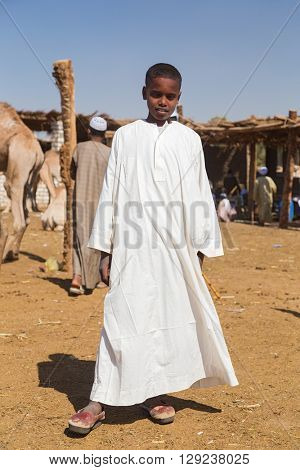 DARAW, EGYPT - FEBRUARY 6, 2016: Local young camel salesmen on Camel market in white robe posing for camera.