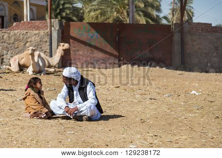 DARAW, EGYPT - FEBRUARY 6, 2016: Local camel salesmen and little girl sitting on the ground at camel market.