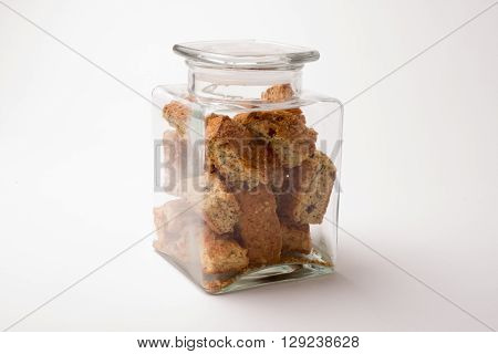 A square glass jar filled with rusks and lid on top on a white background.