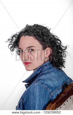 Young Model In Her Mid Twenties Sitting On A Wooden Chair With A Blue Denim Jacket.