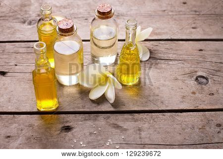 Bottles with essential aroma oil and tropical flowers plumeria on wooden background. Selective focus. Place for text.