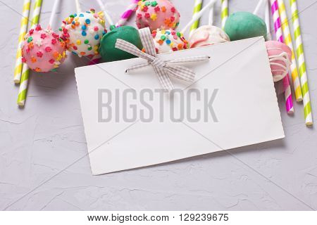 Party background. Colorful bright cake pops paper straws and empty tag on grey textured background. Selective focus. Place for text.