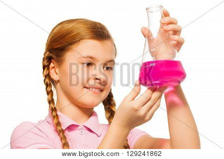 Young chemist, beautiful schoolgirl, pouring pink reagent in glass retort, isolated on white background