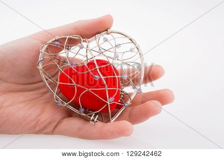 Red heart in a heart shaped cage