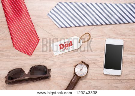 Fathers day composition with greeting card and colorful tie, watch, smartphone and sunglass laid on wooden desk background.