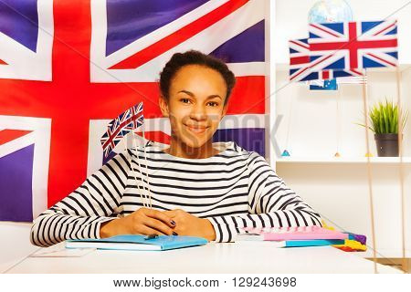 Beautiful teenage African student holding flags of Great Britain, sitting at the desk in the classroom
