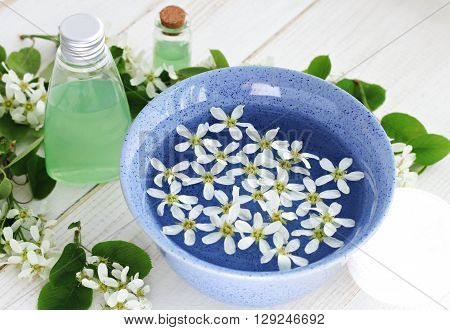 Herbal cosmetic products. Blue ceramic bowl flower water, fresh flowers, cleansing facial tonic. Botanical skincar