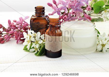 Herbal skincare beauty products. Essential oils, fresh facial cream. Lilac springtime flowers