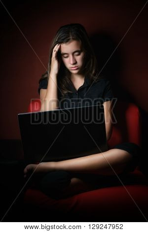 Stressed and exhausted teenage girl working on a laptop computer late at night