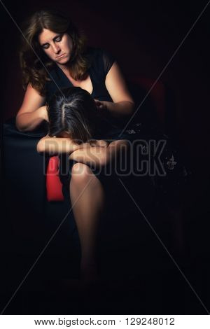 Teenage girl crying while her worried mother tries to comfort her