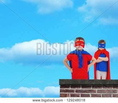 Masked kids pretending to be superheroes against red brick wall