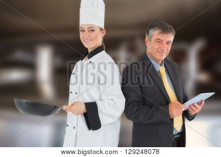 Businessman holding digital tablet and chef with frying pan against large vats of beer