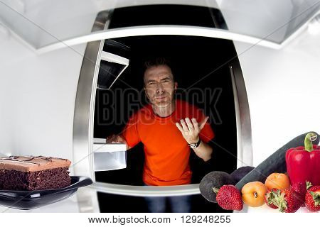 Hungry man looking in the fridge and choosing between cake or fruits and vegetables