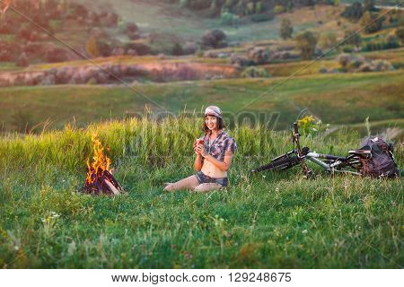 Girl near bonfire - Travel, bicycle tourism, camping: young slim sporty woman tourist brunette at the beautiful nature landscape sitting near the tent by the fire.