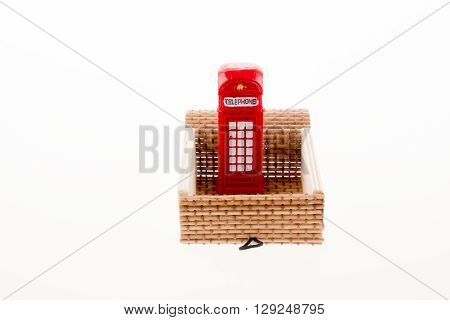 Isolated telephone booth in a straw box on white background
