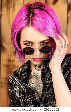 Close-up portrait of a modern girl with bright crimson hair and round sunglasses. Tattoo. Hair coloring. Optics style.