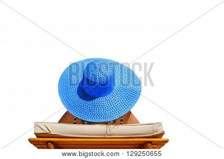 Beautiful woman in a big blue hat on a lounger isolated on white.