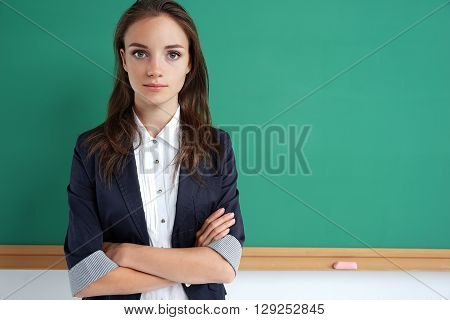 Student folded arms near blackboard. Photo of young student creative concept with Back to school theme